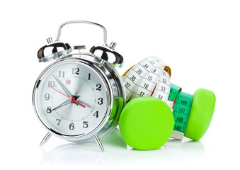 Two green dumbells, tape measure and alarm clock. Fitness and he