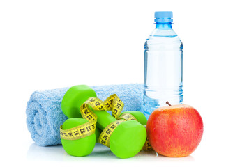 Two green dumbells, tape measure, apple and water bottle