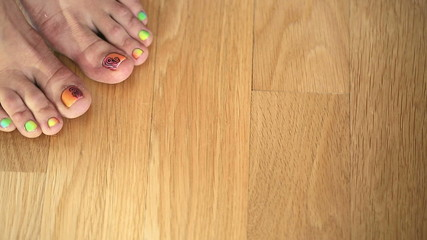 Feet girl on the wooden floor with a nice pedicure