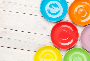 Colorful plates over white wooden table
