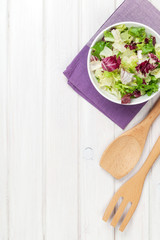Fresh healthy salad and utensils over white wooden table