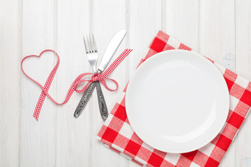 Empty plate, silverware and valentines day heart shaped ribbon