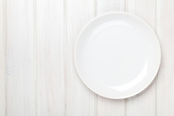 Empty plate over white wooden table