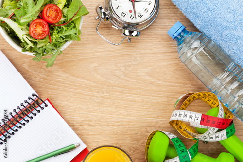 Aluminium Salade Dumbells, tape measure and healthy food over wooden background