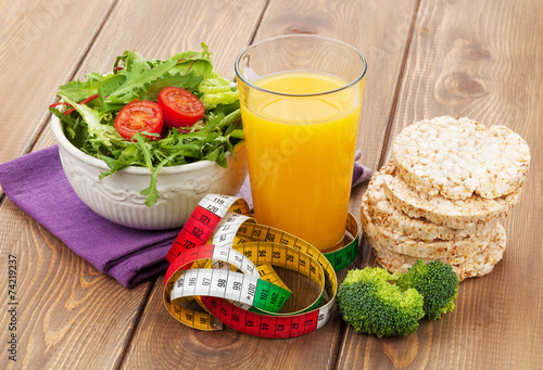 Foto op Aluminium Salade Healthy food and tape measure over wooden table