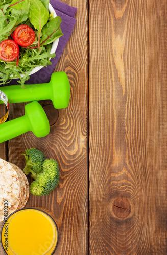 Fotobehang Salade Dumbells, tape measure and healthy food over wooden background