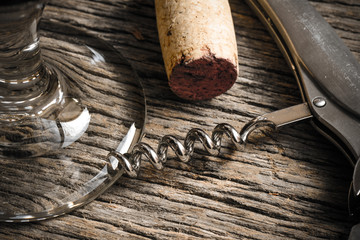 Wine Glass with Cork and Corkscrew on Rustic Wooden Table