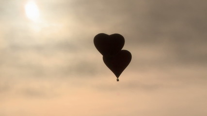 Two air balloons heart-shaped flying in dawn haze