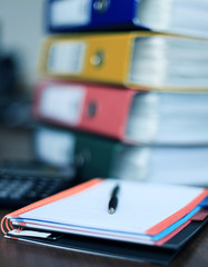 Note book and pen on desk with files on background