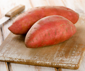 Raw sweet potatoes on a wooden background .