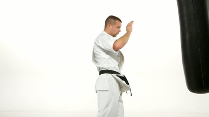 Black belt karate man practicing on the sandbag on white