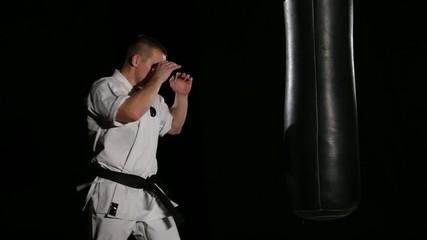 Black belt karate man practicing on the sandbag on black