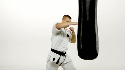 Black belt karate man practicing on the sandbag on white