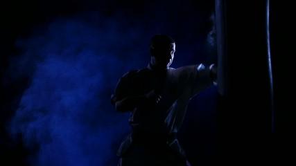 Silhouette karate man practicing on the sandbag on blue