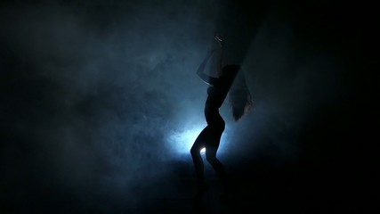 Dancing silhouettes of woman in a nightclub. Slow motion.