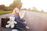 Orphan sits alone on the road with a suitcase poster