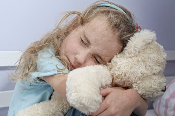 sad lonely girl sitting in the room hugging teddy