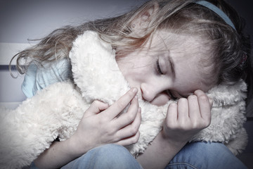 Crying young girl hugging teddy