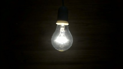 Lit bulb swinging back and forth in front of a wooden board