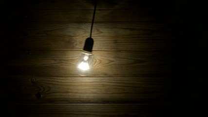 Lit bulb swinging from side to side in front of a wooden board