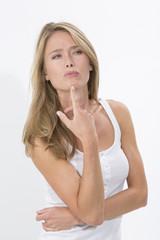 Junge blonde Frau vor weissem Hintergrund, überlegend