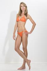 Junge blonde Frau im orangen Bikini