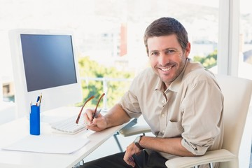 Smiling casual businessman at his desk