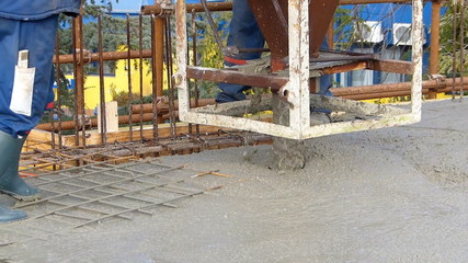 Concrete slab, construction workers working on building
