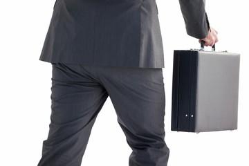 Handsome businessman holding briefcase walking