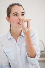 Pretty brunette eating slice of pizza