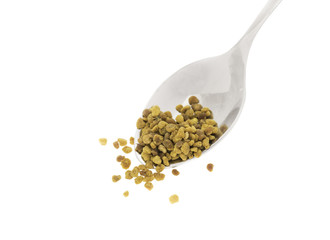 Side view of silver spoon with bee pollen, white background