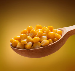 Canned corn in a wooden spoon