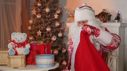 Santa Claus putting gifts in bag isolated near the christmas