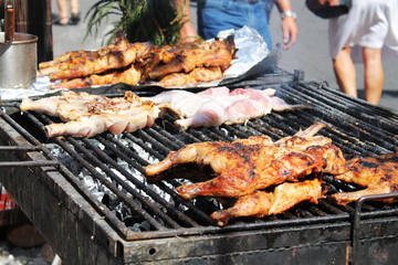 chicken portions on smoking grill, street food