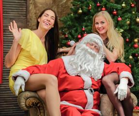 two women having fun and Santa near Christmas tree