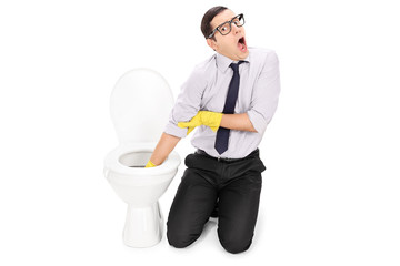 Disgusted man cleaning a toilet with cleaning gloves
