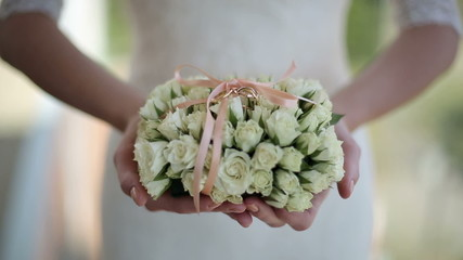 Bride is holding a bouquet of flowers and wedding rings