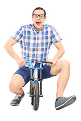 Silly young man riding a small childish bike