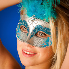 Cute blonde woman with venice mask on her face glamorous portrai