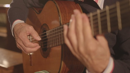 Classical guitarist playing an arpeggio on classic guitar