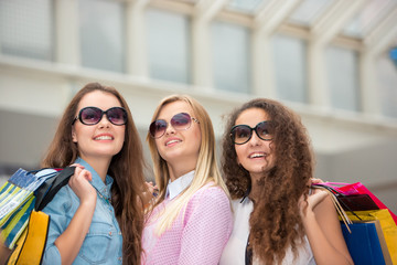 three beautiful girls in sunglasses with shopping bags