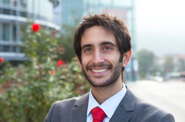 Kreativer Geschäftsmann mit Bart vor Bürogebäude