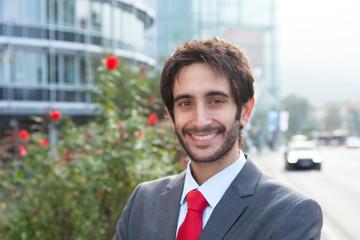 Erfolgreicher Geschäftsmann mit Bart vor Bürogebäude