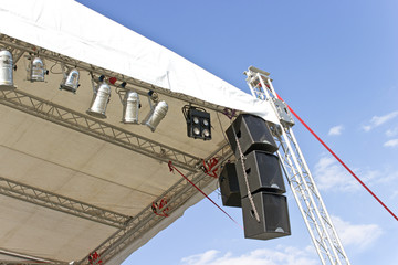 Outdoor concert stage roof construction with speakers  over sky
