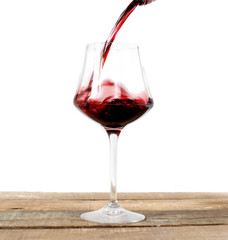 red wine glass over wood against white background