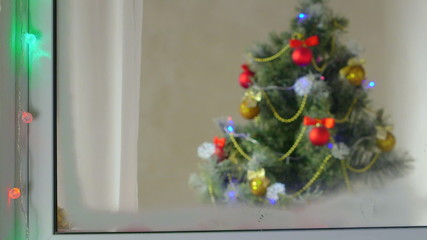 christmas tree with decorations and lights through window