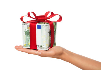 Female hand holding gift made of euro banknotes isol