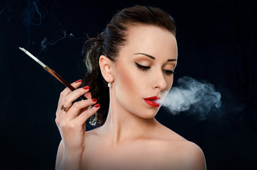 Woman with red lips blowing the  smoke on black background