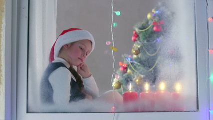Child at the window waiting for Santa on Christmas
