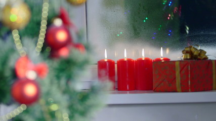 Christmas tree gift box and burning candles at window background